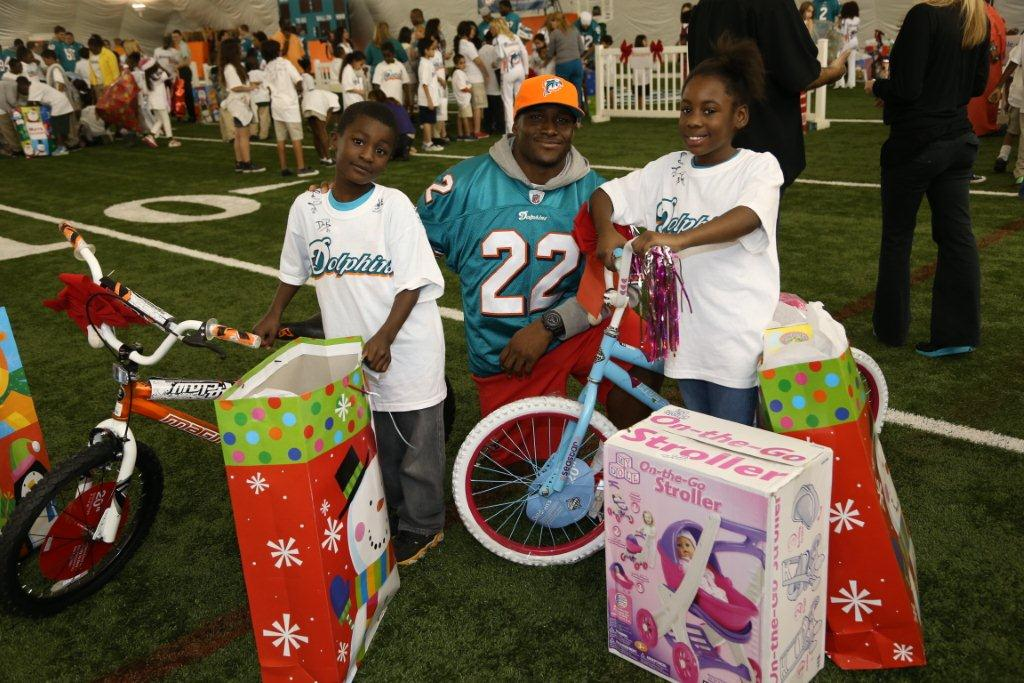 LR Reggie Bush passing out toys to students at the Fins and Kids Holiday Toy event in Davie FL Miami Dolphins host Fins and Kids Holiday Toy Event