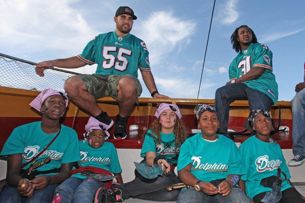 LR 55 Koa Misi and 31 Richard Marshall with students from Camillus House in Miami Dade County at Bluefoot Pirate Adventures Miami Dolphins Take Students to Bluefoot Pirate