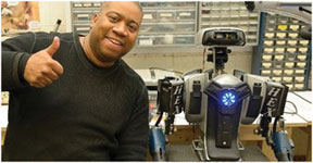 Hygood shown with his latest project, Hex, is a humanoid robot that is leaving observes stunned.