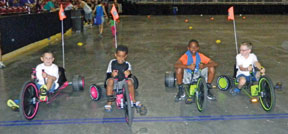 Toddlers participating in Big Wheel Relay Races Field Fay Finale