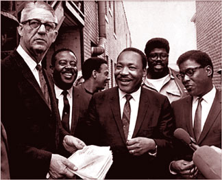 A U.S. Marshal serves Dr. Martin Luther King, Jr. with a temporary restraining order barring a march in  Memphis  without court approval on April 3, 1968. With King, center, are top aides (l to r)  Rev. Ralph Abernathy, Andrew Young, James Orange and Bernard Lee.