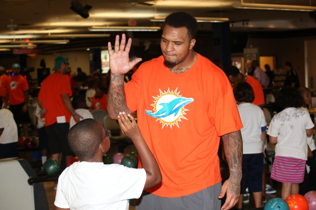 1 Miami Dolphins center Mike Pouncey with student at team bowling event at SpareZ in Davie