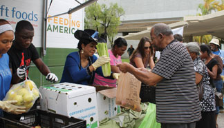 Congresswoman Wilson giving food from Feeding South Florida who brought its Mobile Food Pantry to distribute food to needy families.