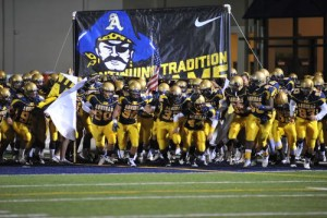 St. Thomas Aquinas High School running on to the football field before game.