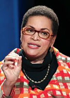 Julianne Malveaux says that President Donald Trump is a show-off, a blow-hard, and an Electoral College-selected buffoon.