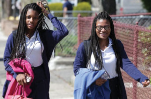 Mya Cook (l) and her sister Deanna Cook attend Mystic Valley Regional Charter School and have served multiple detentions for wearing hair extensions.