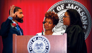 Chokwe Antar Lumumba (l) is sworn-in, becoming Jackson's youngest mayor. Court of Appeals Judge Latrice Westbrooks (right) administers the oath of office to Lumumba as his wife Ebony looks on. (Jay Johnson/Mississippi Link)