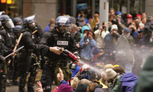 President Trump seemed to endorse police brutality in a speech on Long Island, N.Y. This photo was taken during WTO protests in Seattle, November 30, 1999. Pepper spray is applied to the crowd.      (Wikimedia Commons)