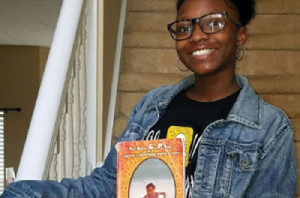 Jordyn Alexis Ash, the granddaughter of author Tyrone Ash, holds a copy of his book.
