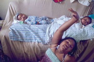 Kayden and Jayden Fluerimond, four months old, rest as their older sister Berlynda, 10, dances in the living room of their aunt's apartment. On August 10, their mother Dacheca Fleurimond passed away at SUNY Downstate hospital after delivering her twin sons.