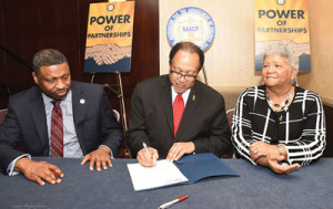 Dr. Benjamin F. Chavis, Jr., the president and CEO of the NNPA, signs a historic agreement with the NAACP, designed to help mobilize voters for mid-term elections and to increase membership for the 109-year-old organization, as NAACP President and CEO Derrick Johnson (l) and Dorothy Leavell, the chairman of the NNPA, look on.