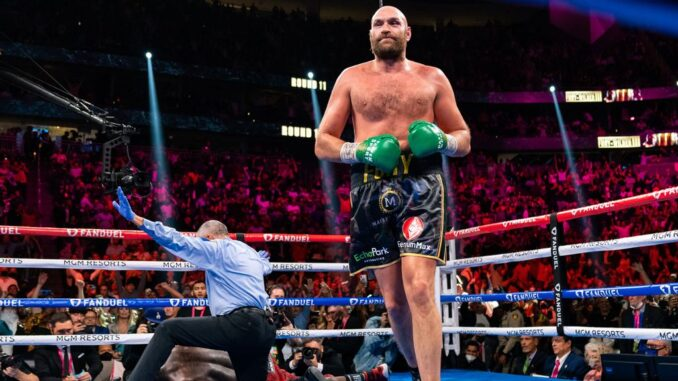 WBC heavyweight champion Tyson Fury (center) floors Deontay Wilder for the third and final time on Saturday as referee Russell Mora signals his 11th-round knockout in Saturday's bout in Las Vegas. (Ryan Hafey/Premier Boxing Champions)