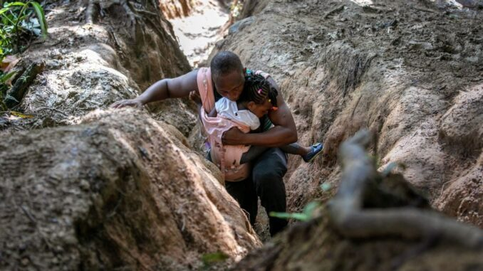 A Haitian father carries his daughter in the Darien Gap, between Colombia and Panama, on Oct. 5. It is the most dangerous passage for migrants walking through the Americas. They often hope to reach the United States, while others stay in Mexico. (John Moore/Getty Images)